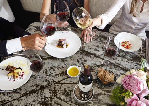 People toasting wine glasses with food